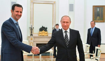 Russian President Vladimir Putin shakes hand with Syrian President Bashar Assad in the Kremlin in Moscow, Russia, Oct. 20, 2015.