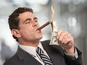 An illustrative image of a white man in a suit lighting a cigar with a burning $100 bill.