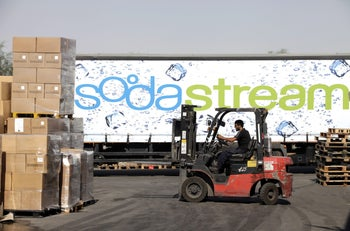 An employee uses a forklift truck to prepare pallets of SodaStream products for export at the SodaStream International Ltd. factory in Mishor Adumim, near Jerusalem, Israel, on Wednesday, Aug. 17, 2011.