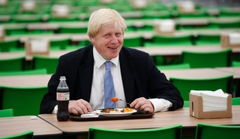 Boris Johnson poses for the media with a plate of food in the athletes' dining hall at the Olympic and Paralympic athlete's village in London, U.K., July 12, 2012.