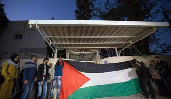 Fatah supporters put up a flag while waiting for Gaza's Hamas rulers to hand over the house of late Palestinian President Yasser Arafat to officials from his Fatah party, Gaza City, November 11, 2015.