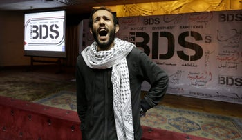 An Egyptian shouts anti-Israeli slogans in front of banners with the Boycott, Divestment and Sanctions in Cairo, Egypt, April 20, 2015.
