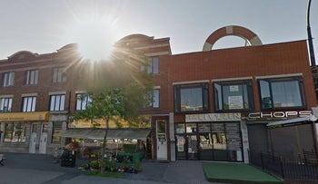 A building in Montreal where a spa is located, with the sun rising just above it.