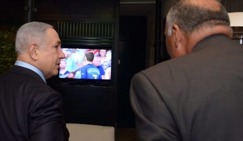 Prime Minister Benjamin Netanyahu and Egyptian Foreign Minister Sameh Shoukry talking during the European Championship final between France and Portugal, July 10, 2016.