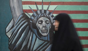 An Iranian woman walks past an anti-U.S. mural painted on the wall of the former U.S. Embassy in Tehran, November 4, 2015.
