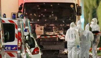 French police forces and forensic officers stand next to a truck July 15, 2016 that ran into a crowd celebrating the Bastille Day national holiday on the Promenade des Anglais.