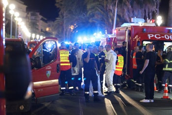 Police officers, firefighters and rescue workers are seen at the site of an attack on the Promenade des Anglais on July 15, 2016, after a truck drove into a crowd in the French town of Nice.