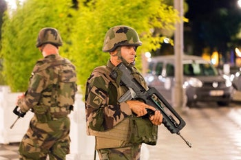 French soldiers stand guard by the sealed off area of an attack in the French resort city of Nice, southern France, Friday, July 15, 2016.