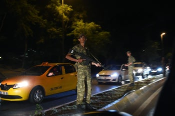 A Turkish security officer stands on guard on the side of the road on July 15, 2016 in Istanbul, during a security shutdown of the Bosphorus Bridge.