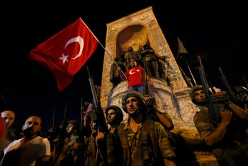 Turkish military stand guard near the the Taksim Square as peiple wave with Turkish flags in Istanbul, Turkey, July 16, 2016.