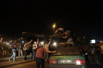 Tanks move into position as Turkish people attempt to stop them, in Ankara, Turkey, late Friday, July 15, 2016.