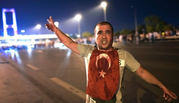 A man covered with blood points at the Bosphorus bridge as Turkish military clashes with people at the entrance to the bridge in Istanbul on July 16, 2016.