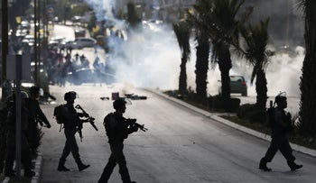 Israeli troops take position during clashes with Palestinian protesters at the entrance of the Palestinian town of al-Bireh, near Ramallah. November 11, 2015.
