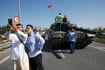 A man takes a selfie next to a military vehicle in front of Sabiha Airport, in Istanbul, Turkey July 16, 2016.