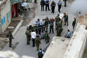 Israeli soldiers and medics gather around the dead body of Palestinian Sa'ad Al-Atrash, who died following an incident at a checkpoint in Hebron on October 26.