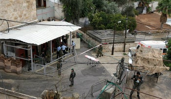 Long-distance view of Border Police officers gathering around the dead body (unseen) of Dania Ershied, 17, who was shot to death at the Hebron checkpoint on October 25, 2015 in disputed circumstances.