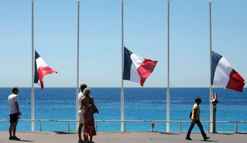 People strolling on the Promenade des Anglais with the French flag at half mast, near the scene of the truck attack in Nice on July 14, 2016.