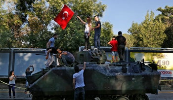 Turkish citizens stand on a damaged Turkish military APC that was attacked by protesters in a street near the Turkish military headquarters in Ankara, Turkey, Saturday, July 16, 2016.