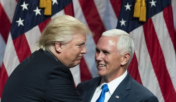 Republican presidential candidate Donald Trump greets his newly selected vice presidential running mate Mike Pence as he takes the stage during an event, July 16, 2016 in New York.