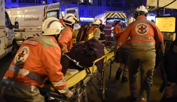 French Red Cross rescue workers evacuate an injured person near the Bataclan concert hall in central Paris, on November 13, 2015.