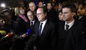 French President Francois Hollande (C), flanked by French Interior Minister Bernard Cazeneuve (L) and French Prime Minister manuel Valls (R) addresses reporters near the Bataclan concert hall in central Paris, early on November 14, 2015.