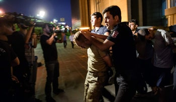Turkish anti-riot police officers escort Turkish soldiers who allegedly took part in a military coup as they are leaving the courthouse at Bakirkoy district in Istanbul on July 16, 2016.