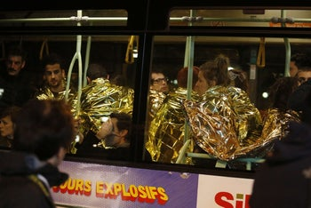People wrapped in life emergency blankets are evacuated by bus, near the Bataclan concert hall in central Paris, on November 14, 2015.