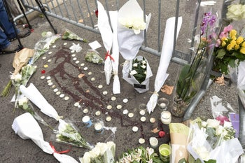 A memorial of flowers and candles surrounds blood stains next to the Bataclan concert hall in Paris on November 14, 2015, following a series of terror attacks that killed at least 120.