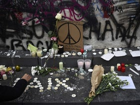 People lay flowers and light candles at the Place de la Republique in Paris following the previous night's terror attacks, November 14, 2015.