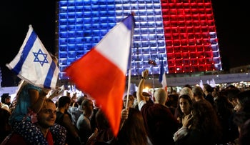 An Israeli and French flag are displayed in front of Tel Aviv city hall at a rally in solidarity with Paris after Friday's terror attacks, November 14, 2015.