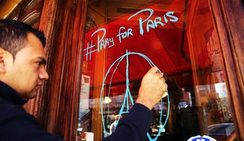 "An employee draws ""Pray for Paris"" on the door of a popular French restaurant in New York City a day after the attacks in Paris, November 14, 2015."