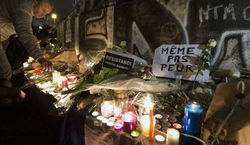 A man lays flowers at a makeshift memorial in tribute to the victims of the Paris'attacks at the place de la Republique in Paris.