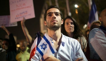 An Israeli man holding an Israeli and a French flag at a solidarity demonstration with France following the attacks in Paris in Tel Aviv, November 14, 2015.