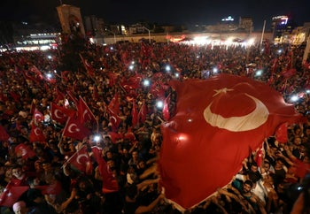 Supporters of Turkish President Tayyip Erdogan wave national flags as they gather at Taksim Square in central Istanbul, Turkey, July 16, 2016.