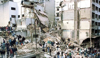 Rescue workers search for survivors and victims in the rubble left after a bomb destroyed the Buenos Aires headquarters of the Argentine Israeli Mutual Association, killing 85. July 18, 1994.