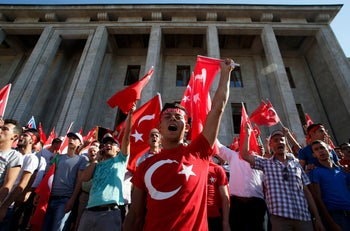 Supporters of Turkish President Tayyip Erdogan wave flags outside parliament building in Ankara, Turkey, July 16, 2016.