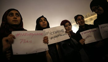 Hijabi Muslim girls hold posters reading '#NotinMyName' during a rally in tribute to the victims of the Paris terror attacks. Turin, Italy November 14, 2015.