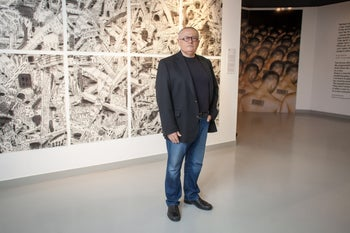 Founder and curator Raphie Etgar stands in front of artwork at the Museum on the Seam in Jerusalem.