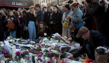 People pay their respect to the victims at the site of the attacks on restaurant Le Petit Cambodge  and the Carillon Hotel, Paris, November 15, 2015.