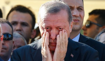Turkish President Recep Tayyip Erdogan wipes his tears during the funeral of Mustafa Cambaz, Erol and Abdullah Olcak in Istanbul, Sunday, July 17, 2016.