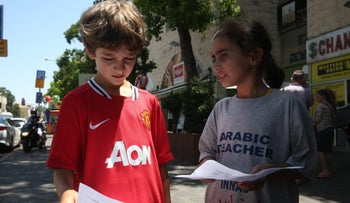 Innas, 12, teaches a 10-minute Arabic lesson to a child walking in Jerusalem near the table and bench she and her family have set up on Emek Refaim Street.