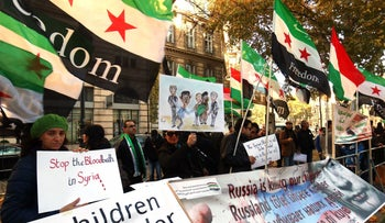 Protesters, holding Syrian flags and posters calling for an end to the bloodbath in Syria, gather near Hotel Imperial in Vienna, Austria, Saturday, Nov. 14. Global powers met there to try to find a diplomatic solution to the Syrian conflict.