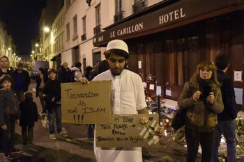 A Muslim man holds placard reading 'Terrorism is not Islam. Islam is like this flower. Terrorism has no religion' during a gathering at 'Le Carillon' restaurant, one of the site of the attacks in Paris, November 15, 2015.