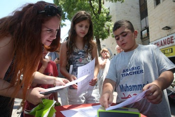 Muhammed, 14, points to something on his lesson sheet while a woman and young girl look on.
