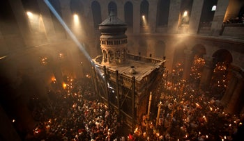 Christian pilgrims hold candles at the Church of the Holy Sepulchre during the ceremony of the Holy Fire in Jerusalem's Old City, April 14, 2012.