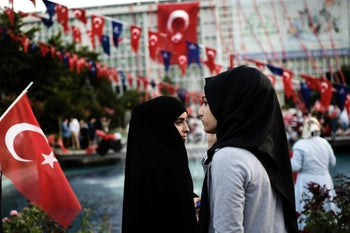Two women attend a pro-government demonstration outside the city hall in Istanbul, July 17, 2016.
