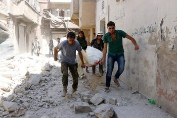 Civil defense workers evacuate a body following reported airstrikes in the rebel-controlled neighborhood of Maysar in Aleppo, July 17, 2016.