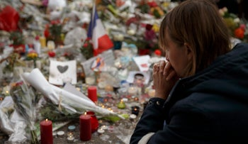 A woman prays as she pays her respect in front of a floral tribute near the Bataclan concert hall after Friday's terror attacks in Paris, Monday, Nov. 16, 2015.