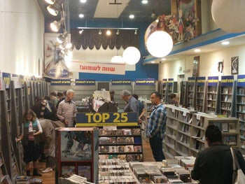 The final sale at Tower Records in Ra'anana, November 2015. Several customers browse through mainly-empty racks of music CDs and DVDs.