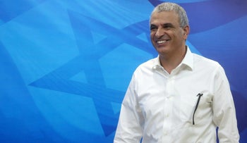 Finance Minister Moshe Kahlon walks past a giant projection of the Israeli flag.